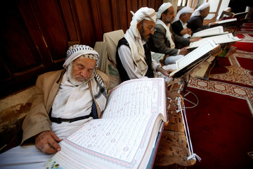 A man rests while reading the Koran at the Grand Mosque, during the holy month of Ramadan in Sanaa