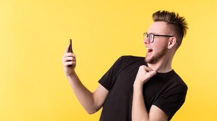 Portrait of shocked hipster guy on yellow background. Young emotional man got scared by information in his smartphone. Copy space.
