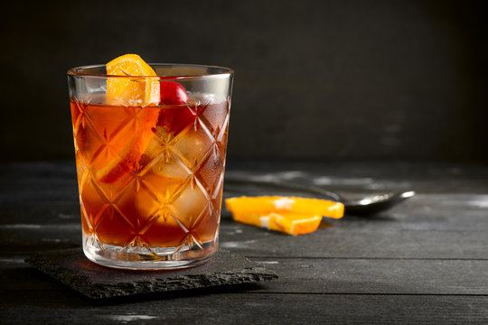 Whiskey sour cocktail with a slice of orange, cherry and ice, a classic alcoholic drink on black background