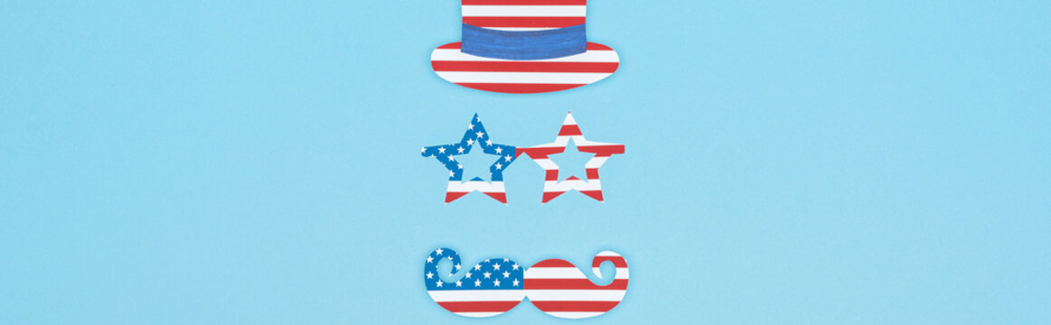 panoramic shot of paper cut mustache, glasses and hat made of usa flags on blue background