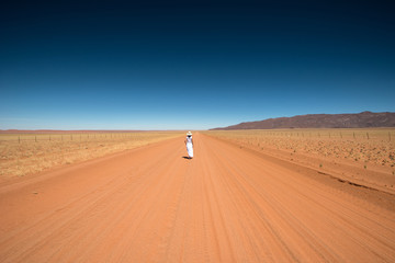 Solitary woman in a namibian road