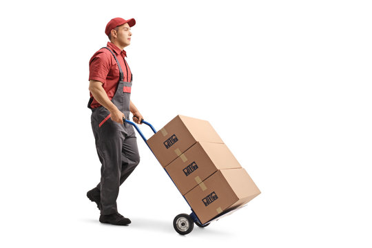Young male worker in a uniform pushing boxes on a hand truck