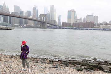 A model poses during a photo shoot on the shore of Brooklyn Bridge Park in the Brooklyn borough of New York