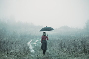young girl with umbrella in autumn field