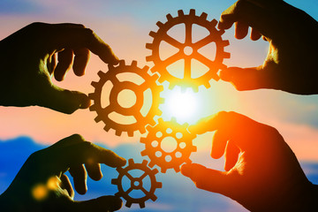 gears in the hands of people against the sky. the mechanism of interaction. teamwork.