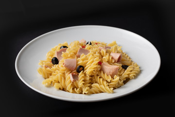 Pasta with tuna and tomatoes in a white plate on black