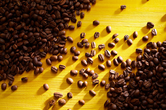 Roasted coffee beans on colorful yellow wood