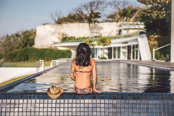 backview of a beautiful tattoed woman sitting at a pool
