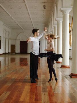 Sensual artistic couple dancing in ballroom