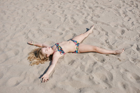 Little girl laying on the sand of the beach from above