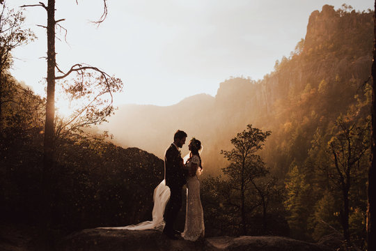 A couple's silhouette in front of a mountain at sunset.