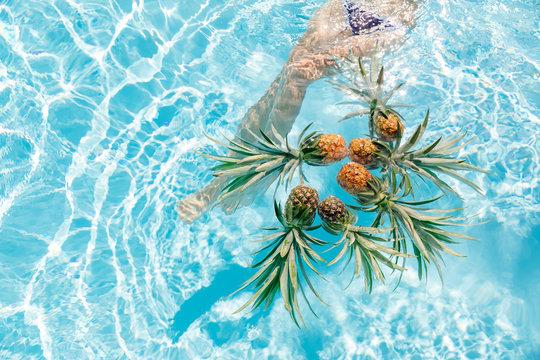 Woman's legs near floating pineapple