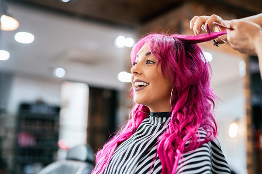 Beautiful woman getting haircut by hairdresser in the beauty salon