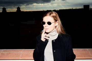 Elegant blonde woman in sunglasses smoking a cigarette on the ro