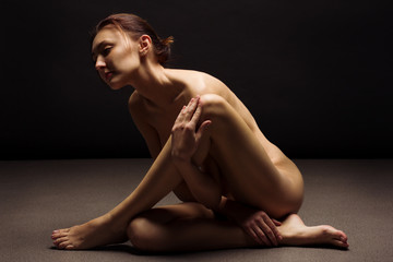 Fashion studio shot of naked slim woman. Nude yoga girl on black background.