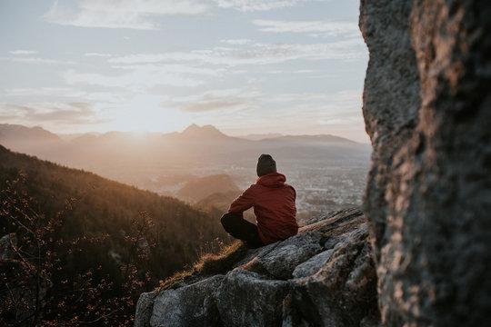 Climber sat on mountain looking at sunset