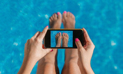 Woman taking pictures of her feet nails in the pool