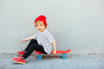 Blonde kid sitting on red skate.