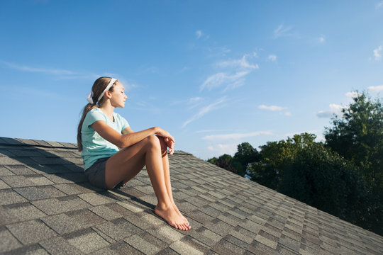 Roof: Girl Sits On The Roof Of A House Daydreaming