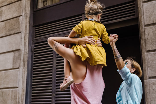 Father carrying daughter on his shoulders while mother walking beside them