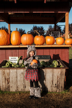 Asian Girl in a Wolf Costume Holding a Pumpkin During Fall Season