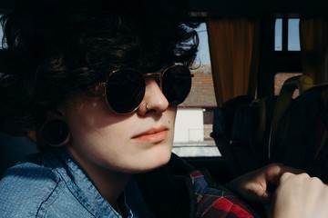 Close up portrait of a female model with sunglasses traveling by bus