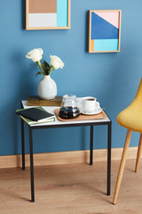 Modern table with coffee, flowers and books.