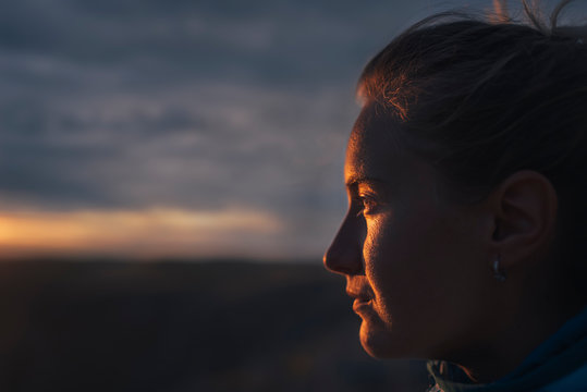 Close up of woman standing outdoors during sunset