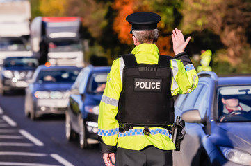 Belfast, Northern Ireland. 24 Nov 2016 - An armed PSNI officer waves on traffic during a vehicle checkpoint. Credit:  Stephen Barnes/Alamy Live News