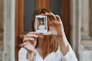 Woman holding instant photo in front of her face