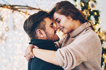 Romantic couple in love feeling happiness about their romance spending christmas eve together, woman and man enjoying perfect relationships and spending winter vacations in cozy home interior .