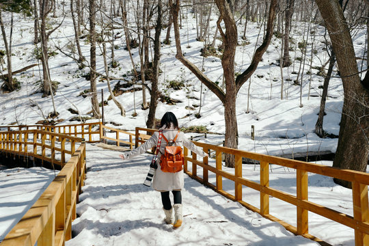Traveler carrying a camera and backpack walking on a wooden trestle covered with snow, Sapporo, Hokkaido, Japan