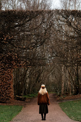 blode woman looking to a huge  dried bush in a garden