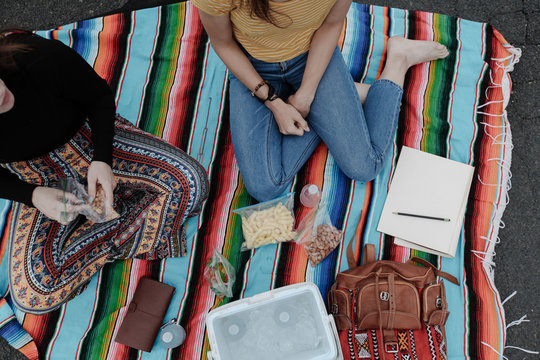 teens sitting on blanket with lunch