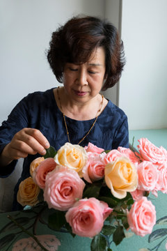 Asian woman  arrange flowers indoor