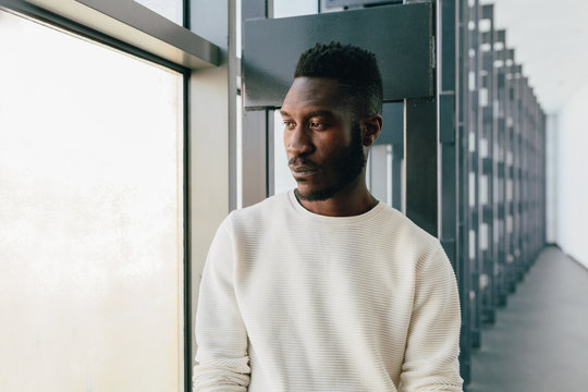 Young black man with pensive expression looking out window