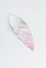 An ombre pink to white painted leaf cut into four seperate parts