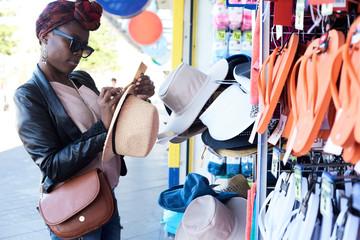 Stylish woman shopping hats in souvenir.