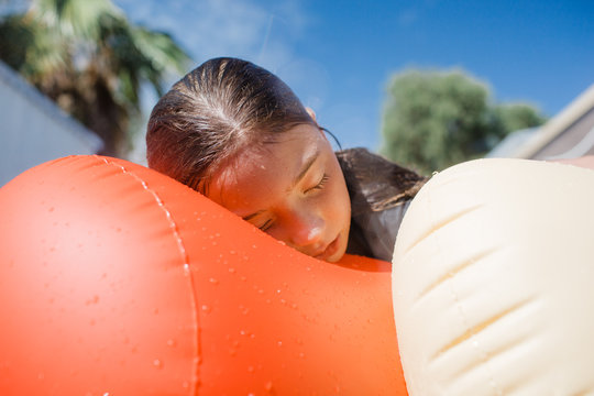 Young girl relaxes after a big day of swimming on top of a pool inflatable on a hot summer day