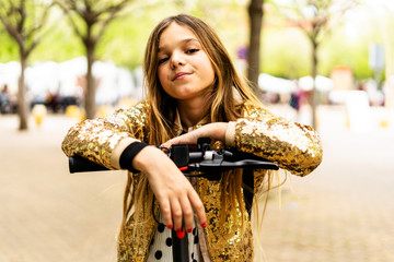 Portrait of girl wearing golden sequin jacket leaning on handlebar of E-Scooter