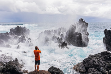 USA, Hawaii, Big Island, Laupahoehoe Beach Park,Man taking pictures of breaking surf at the rocky coast