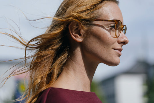 Profile of young woman with glasses and windswept hair