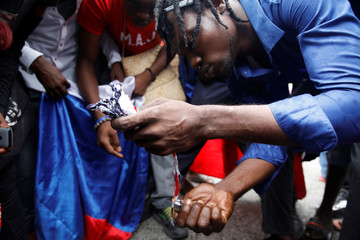 A protester tries to burn a ripped US flag, as another holds a Russian flag in the background, during a protest outside of the Legislative Palace in Port-au-Prince