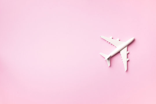 Travel, vacation concept. White model airplane on pastel pink color background with copy space. Top view. Flat lay. Minimal style design.