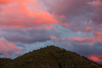 Beautiful pink, purple, and peach colored clouds at sunset over a forested mountain peak - Sangre de Cristo Mountains near Santa Fe, New Mexico