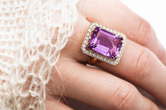 Beautiful golden ring with a large amethyst on a female hand, close-up