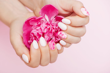 Wall Mural - Peony flower in beautiful woman's hands with trendy nail art on pink background.