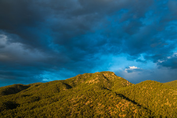 Beautiful evening sky over a mountain peak clad in a juniper and pine forest - Sangre de Cristo Mountains near Santa Fe, New Mexico