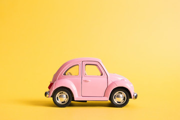 Omsk, Russia - May 26, 2019: Pink retro toy car on yellow background. Valentines day. 8 March. Summer travel concept. Taxi.