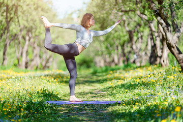 Picture of woman doing yoga standing on blue rug in forest
